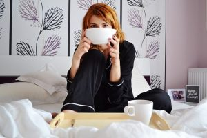 a girl drinking coffee in a bed