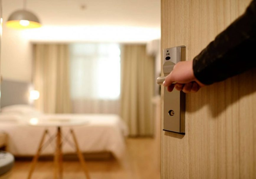 image of a person opening door to room