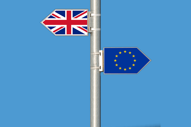 british and eu flags on a pole