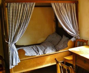 four poster bed in rustic room
