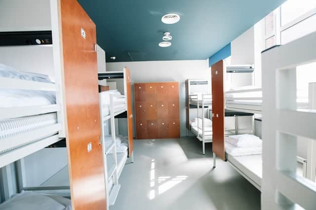hostel room with bunk beds and lockers
